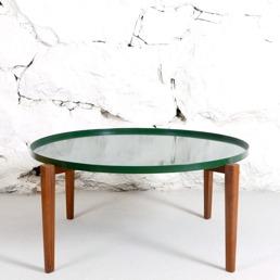 Runt soffbord med träben och grön metallskiva. Fogelmarck Form i samarbete med Duett.