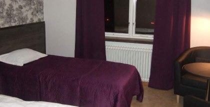 Hotellrum med dusch, wc, tv och kylskåp på rummet. Gratis wifi och bilparkering.