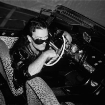 LYNN GOLDSMITH Bono in Corvette smoking looking over glasses low on nose