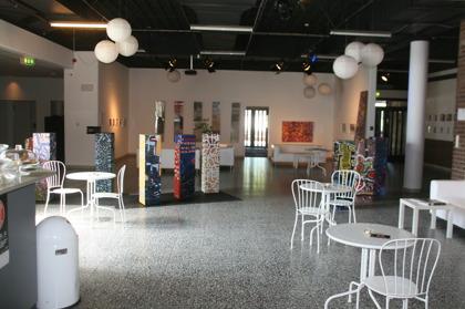 Huvudentrén till Livsglädjemässan syns i bakgrunden. Här kommer även Livsglädjemässans kafeteria att hålla till. I detta rum finns mässans huvudplatser och gränsar till övriga mässalar.