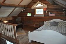 En bild på sovloftet med dubbelsäng och liten sittgrupp