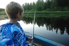 Liten pojke som metar från båt