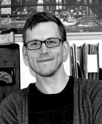 Foto på Richard Fransson. Man med glasögon, kort frisyr och svart t-shirt och grå kofta.