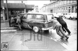 Tre män knuffar på en gammal bil som antagligen fått motorstopp.