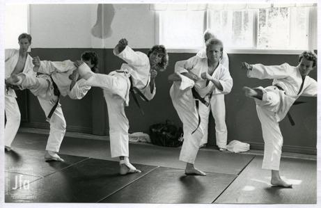 Foto på fem män i vita dräkter som står på vadderade mattor och måttar sparkar.