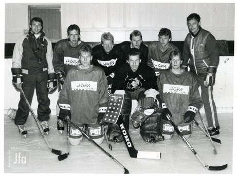 Foto på nio män i ishockeyutrustning uppställda för foto på en isrink.