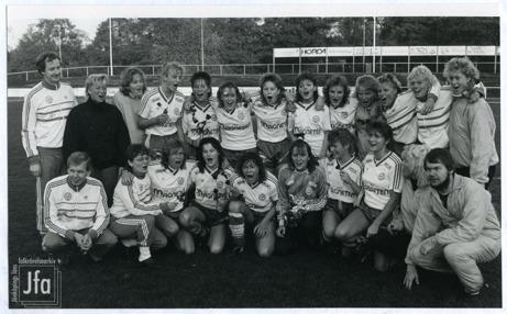 Foto på ett tjugotal fotbollsklädda unga damer uppställda på en fotbollsplan för fotografering. Även två män som förefaller vara tränare är med på fotot.