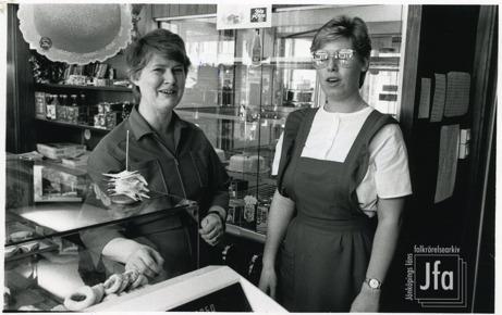 Foto på två kvinnor bakom kassan på ett konditori. I en monter kan man skymta kakor.