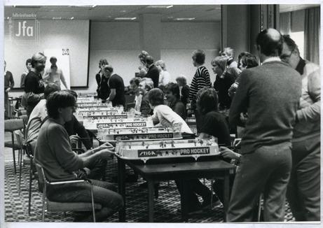 Foto på ett tjugotal människor i en lokal med heltäckningsmatta. På bord finns ett antal bordshockeyspel uppställda. Spel pågår.