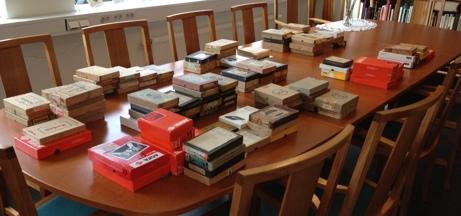 Ett fyrtiotal askar med glasplåtar ligger på ett bord.