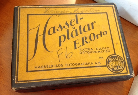 Närbild på pappask av märket Hasseblad. Asken är gul och grå.