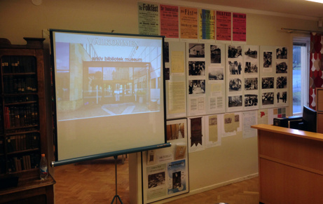 En skärm uppställd i en dörröppning med ett bildspel. På väggarna en utställningsmaterial i form av fotografier och affischer. Foto: Richard Fransson