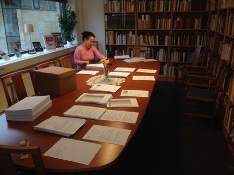 Anna Sundin sitter vid sammanträdesbordet på folkrörelsearkivet. På bordet högar med papper. Foto: Richard Fransson