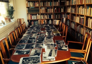 Ett trettiotal fotografier liggande på ett långbord. Foto: Richard Fransson