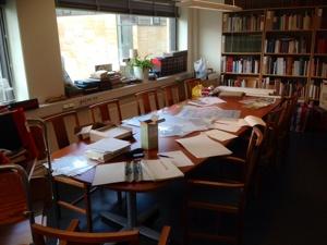 Foto över långbord. På bordet ligger papper och annat kontorsmaterial. Längs med väggarna bokhyllor. Foto: Richard Fransson
