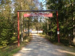 """Grusväg med skog på sidorna. Längre fram röda stolpar med en skylt med texten: """"Välkomna till IOGT-NTO Bäckalyckan.""""Foto: Richard Fransson"""
