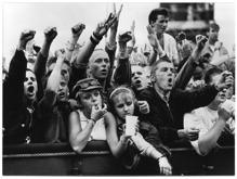 Fotografi på del av publikhav, unga män och kvinnor, som lutar sig över ett staket framför en scen.