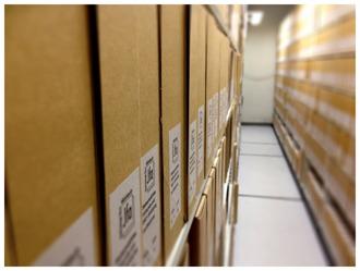Färgfotografi av arkivkartonger på arkivhyllor.
