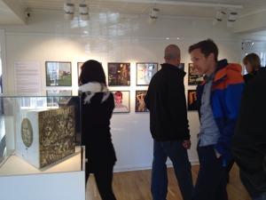 Människor går runt och tittar på skivomslag. Från invigningen av utställningen 15/5 2015.
