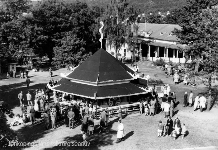 Vy över människor i en park. I mitten av bilden en rund byggnad med lotteri och spel.