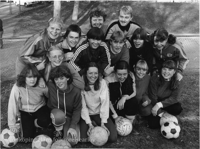 Foto på 14 unga damer och en man. På marken framför ligger sju fotbollar.