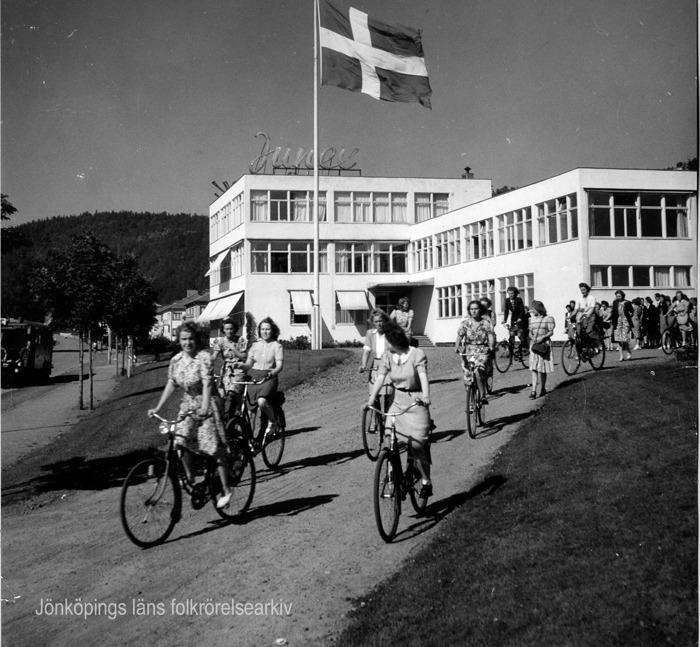 """Foto på en grupp med kvinnor som cyklar. I bakgrunden en vit fabrik med en neonskylt på taket med texten """"Junex"""". I mitt av bilden en hissad svenska flagga som fladdrar i vinden."""