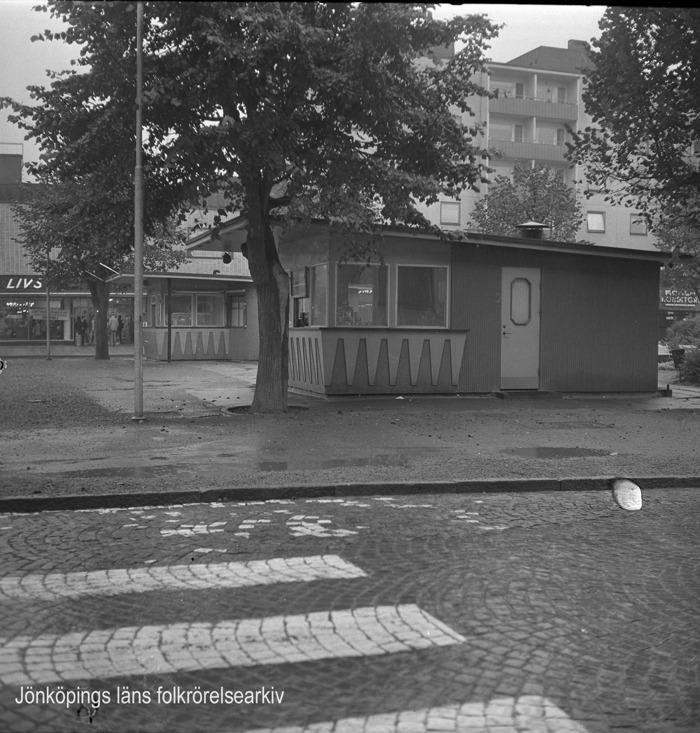Foto på övergånsställe. Efter övergångsstället ligger små kioskbyggnader.