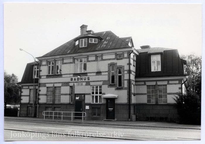 """Foto på stort stenhus. Ovanför ingången står texten: """"Badhus 1910""""."""