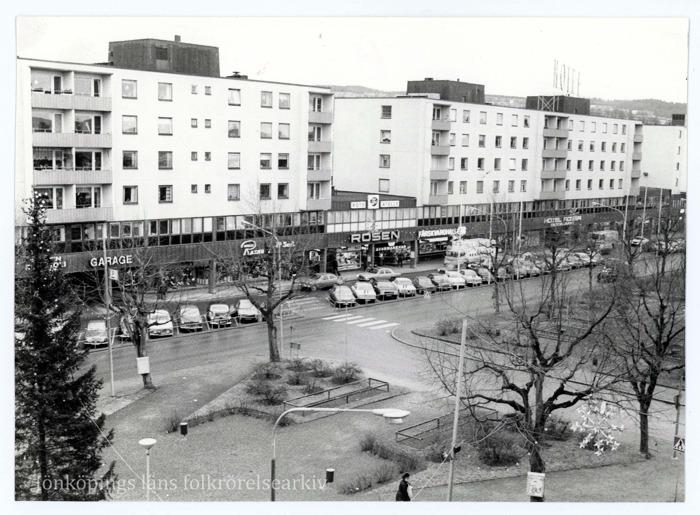 Foto på höghusbebyggelse i centrala Huskvarna, bland annat ett köpcenter. I mitten en esplanad med träd och gångar.