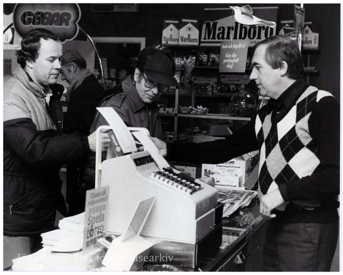 Foto på fyra män i en kiosk. En av dem bakom kassan och de andra framför.