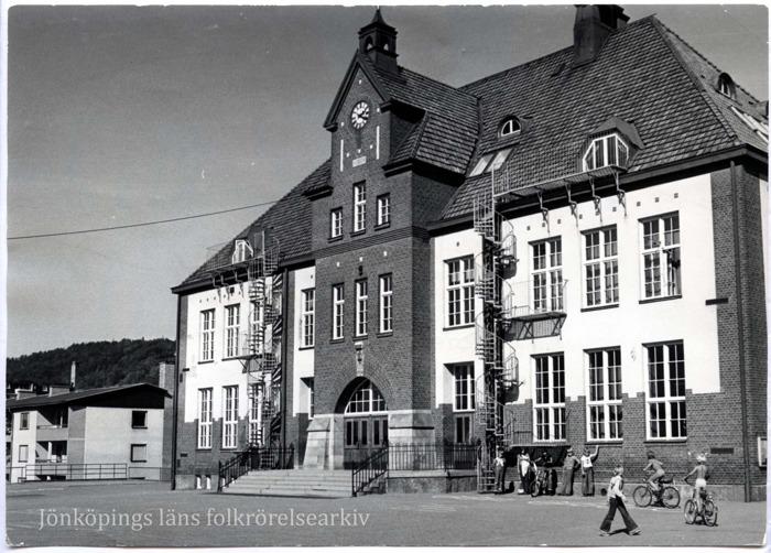 Foto på stor tegelbyggnad. Längs med fasaden står en grupp med skolever.