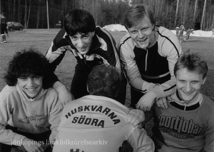"""Foto på fem stycken fotbollskillar som hukar framför kameran. En av dem har vänt ryggen till för att visa texten på baksidan av jackan: """"Huskvarna Södra""""."""