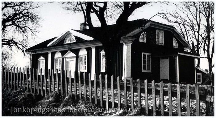 Foto på trähus med vita detaljer kring fönstren. Framför huset ett staket.