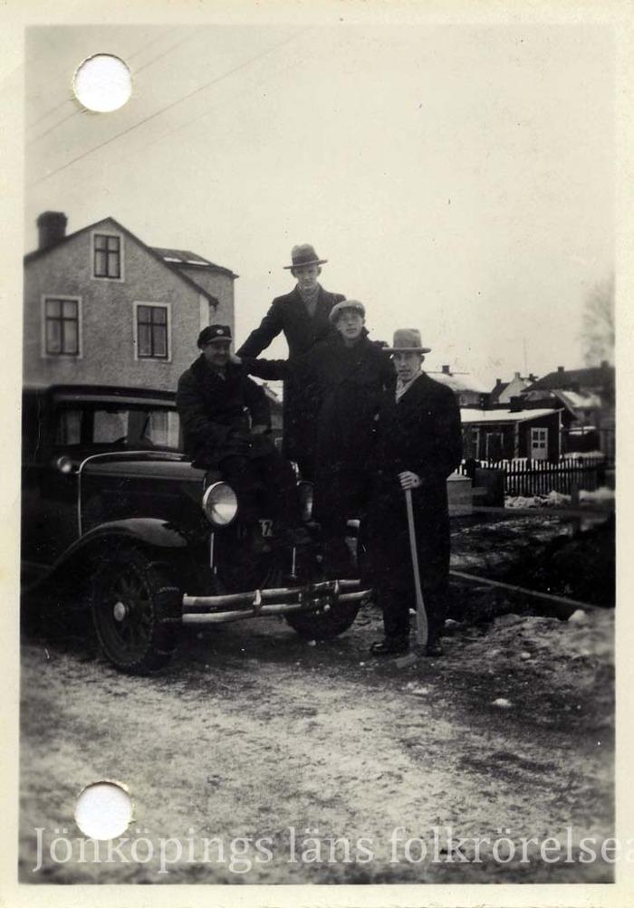 Foto på fyra män. En sitter på motorhuven till en bil, två står på kofångaren och en står bredvid med en bandyklubba i handen. I bakgrunden hus.