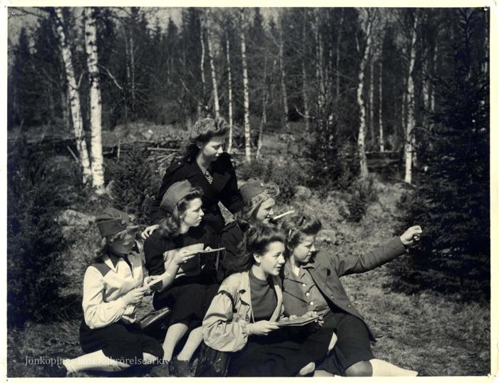 Foto på sex unga kvinnor i skogen. De ser ut att avläsa någon slags karta och en av dem pekar bort mot något.