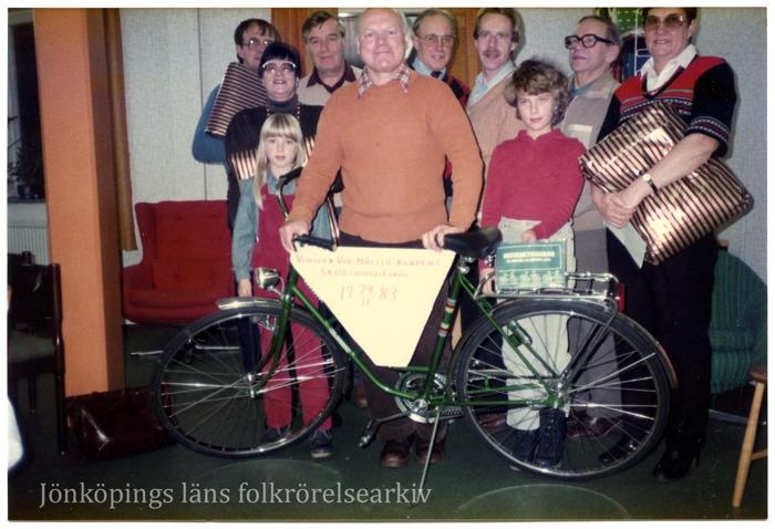 Färgfoto på en grupp människor som håller paket i händerna. En av dem  håller en cykel.