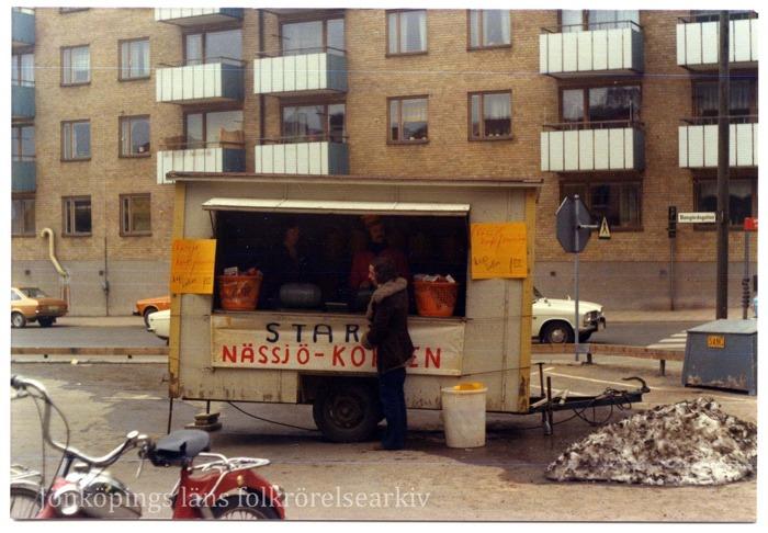 """Färgfoto på en person som står framför ett bås på hjul. I båset står två personer. """"Start Nässjö-Korpen"""" är skrivet på en skylt på båset. I förgrunden en röd moped. I bakgrunden höghus. Vid sidan av b"""