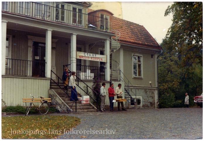 """Fem personer står vid en trappa som leder upp till ett stort trähus. Några av dem står vid ett bord. Ovanför finns en banderoll med texten """"Start Nässjö-Korpen""""."""