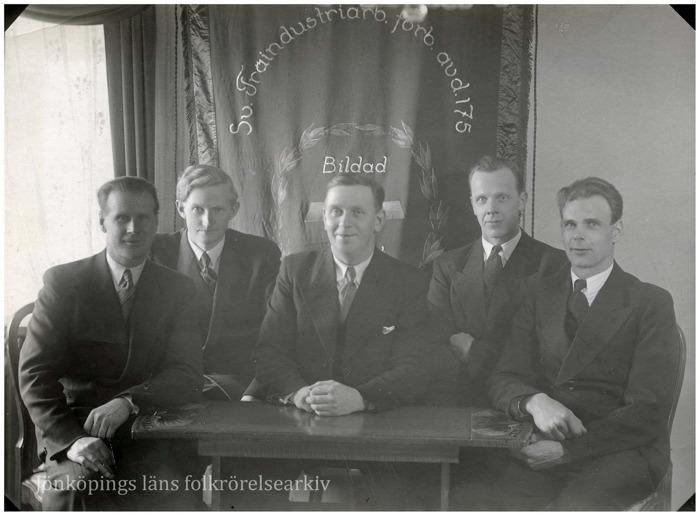 Foto på fem män i kostym som sitter framför en fana.