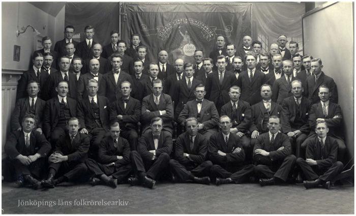 Foto på en grupp män, runt 50 stycken, några sittande, några stående framför en fana.