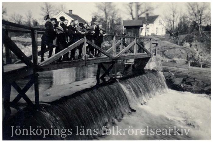 Foto på en grupp med pojkar som står på en träbro som leder över en fors.