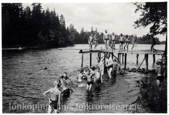 Foto på badande barn och några vuxna vid en skogssjö.