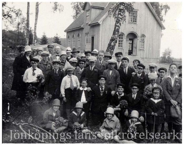 Foto på en grupp finklädda människor i alla åldrar som står framför en träbyggnad. Runtomkring ser det ut att vara skog.