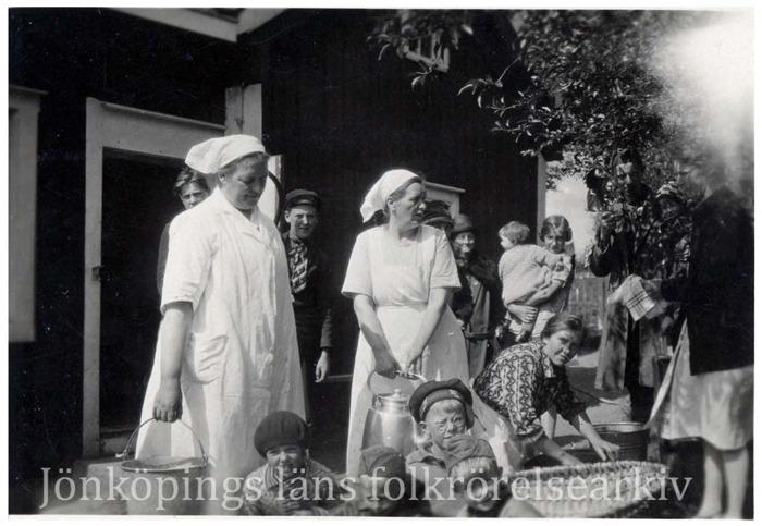 Foto på barn som sitter framför några vuxna kvinnor som har vita rockar på sig. Förmodligen är det matlagning på gång.