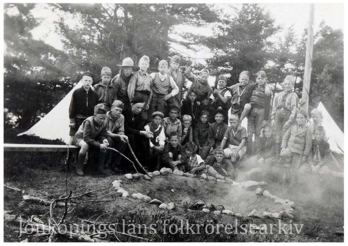 Foto på ett tjugotal barn som sitter vid en eldgrop och grillar. I bakgrunden tält.