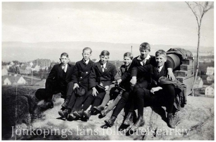 Foto på sex pojkar som sitter på bergshäll vid en kanon. I bakgrunden en stadsvy över Jönköping.