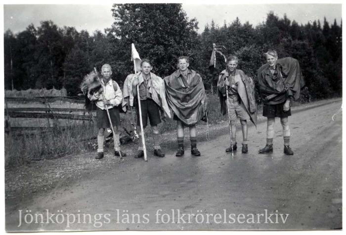 Foto på fem blöta pojkar på en grusväg. Några av dem har har vandringsstavar och regnkappor över sig själv och sin packning.