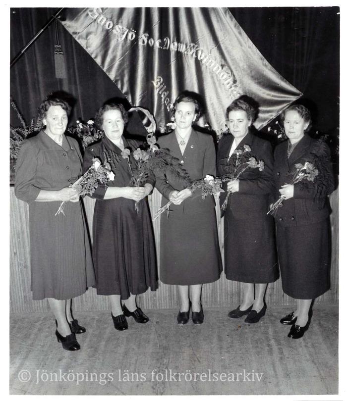 Fem kvinnor står med blommor i händerna framför en fana.