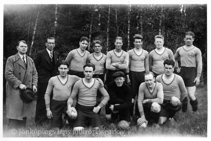 13 män uppställda för foto. 11 av dem har matchdräkt för fotboll på sig. Två stycken har kostym och rock. Ser ut att vara äldre än 1950-talet. I bakgrunden skog.