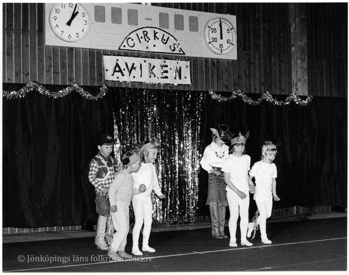 """Sex stycken barn utklädda till indianer och cowboys uppträder i idrottshall. Ovanför en skylt med texten """"Cirkus Åviken""""."""